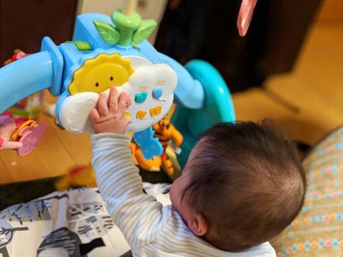 おすわりしてプーメリーで遊ぶ赤ちゃん